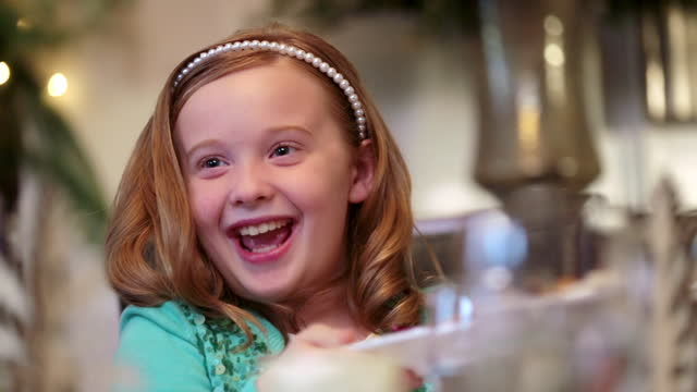 Cute young girl helps pass plates of food around table for Christmas dinner