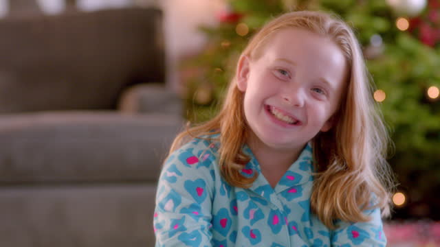 Cute young girl laughs in front of Christmas tree