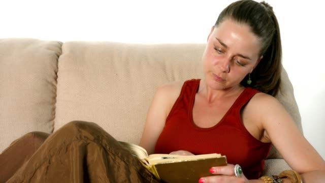 süße junge mädchen auf der couch liegen und ein buch zu lesen - buchdeckel stock-videos und b-roll-filmmaterial