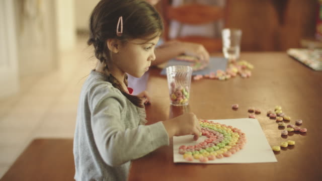 cute young girl making a rainbow out of breakfast cereal - children only stock videos & royalty-free footage