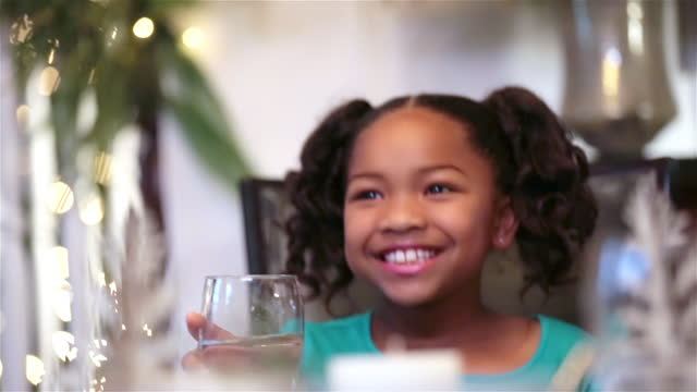 cute young girl raises glass to toast and clink with family at dinner table - einen toast ausbringen stock-videos und b-roll-filmmaterial