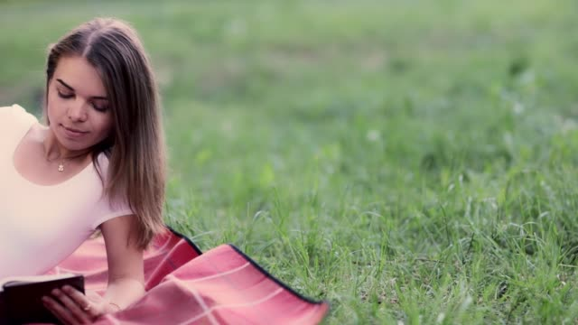 cute young girl reading a book in the park - portrait with bible - hd video - video portrait stock videos & royalty-free footage