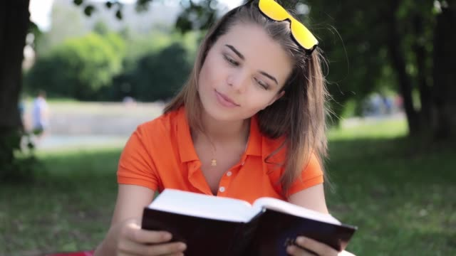 cute young girl reading a book in the park - portrait with sunglasses - hd video - video portrait stock videos & royalty-free footage