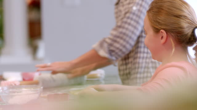 Cute young girl rolls and flattens cookie dough in the kitchen, looks up to mother