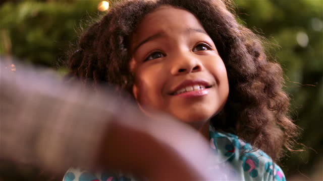 cute young girl sits beneath christmas tree, gazing up at parents expectantly - christmas present stock videos and b-roll footage