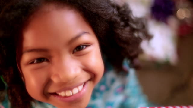 cute young girl with christmas present looks up and smiles at camera - home movie stock videos & royalty-free footage