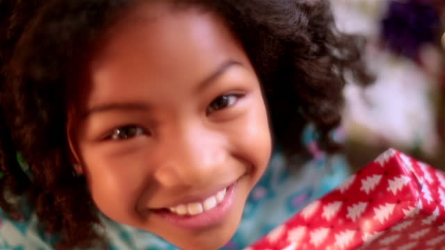 Cute young girl with Christmas present smiles at camera