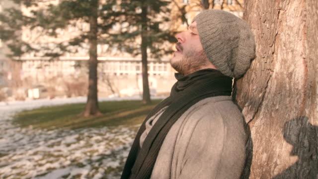 vídeos de stock, filmes e b-roll de bonito jovem encostado em uma árvore no parque e contemplando o pensamento sobre os seus problemas - tristeza