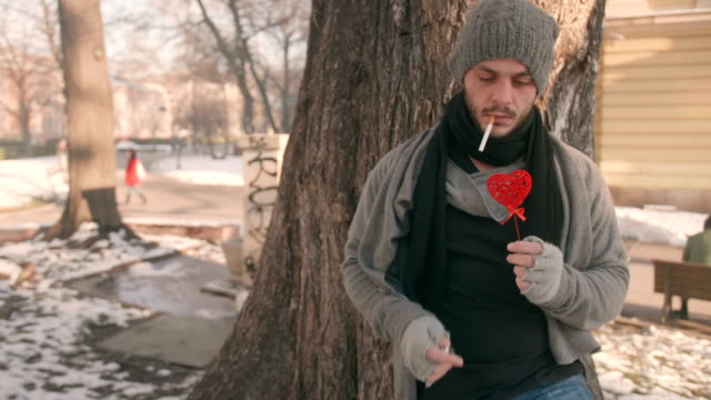 cute young man leaning on a tree in the park holding a heart shape thinking contemplating about his love issues and smoking a cigarette - relationship breakup stock videos & royalty-free footage