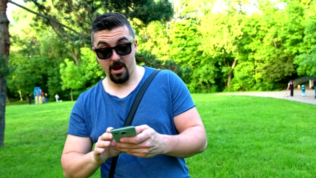 Cute young man using his smart phone while walking in the park