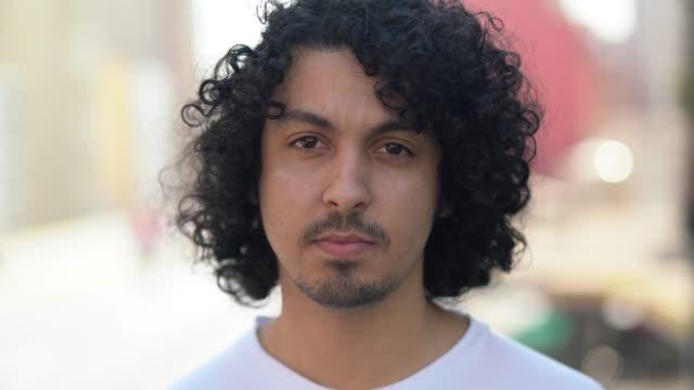 vídeos de stock e filmes b-roll de cute young men with curly hair portrait - young men