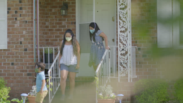 cute young native-american family walk out the door of their home wearing protective face masks - family with two children stock videos & royalty-free footage