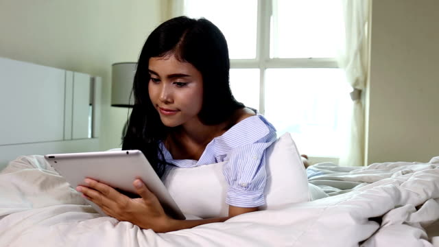 cute young woman lying on bed using touchpad and smiling - touchpad stock videos & royalty-free footage