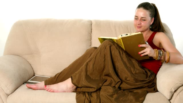 cute young woman lying on the couch and reading a book - quality control stock videos and b-roll footage