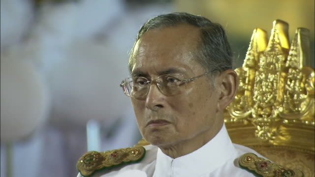 2 cuts king bhumipol seated at prince mahidol award ceremony tilting up from feet to bust shot /close up of many medals on left side of king... - king of thailand stock videos and b-roll footage