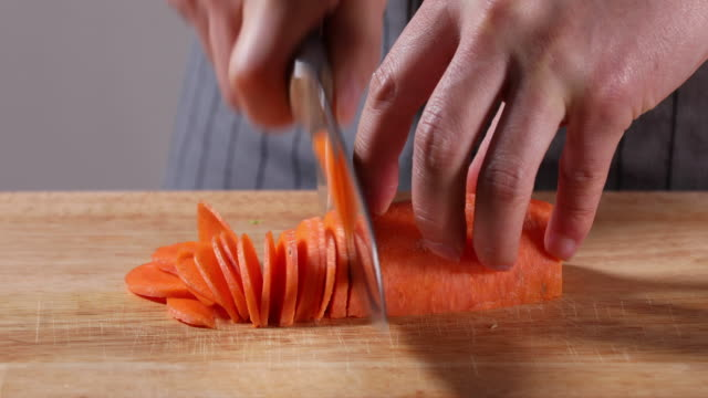 vidéos et rushes de cutting a carrot with a knife on the chopping board - carotte