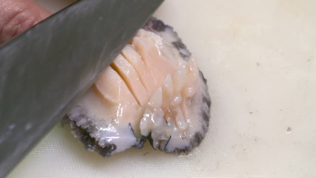 cutting a raw abalone with a knife (korean food) - seashell stock videos & royalty-free footage