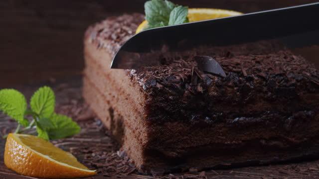 vidéos et rushes de couper une tranche de gâteau au chocolat décorée d'orange fraîche et de menthe. plan rapproché extrême - couteau de cuisine