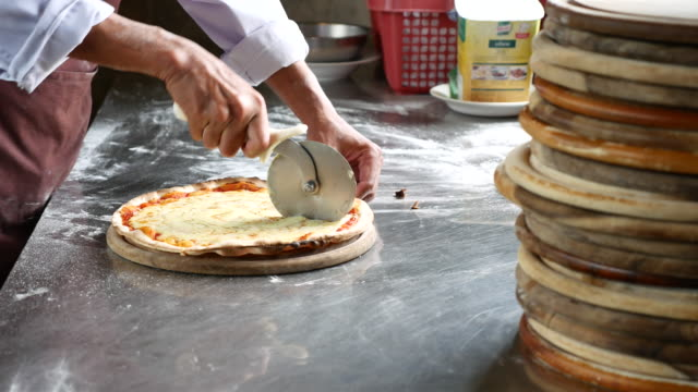 cutting a slice of pizza - cucina mediterranea video stock e b–roll