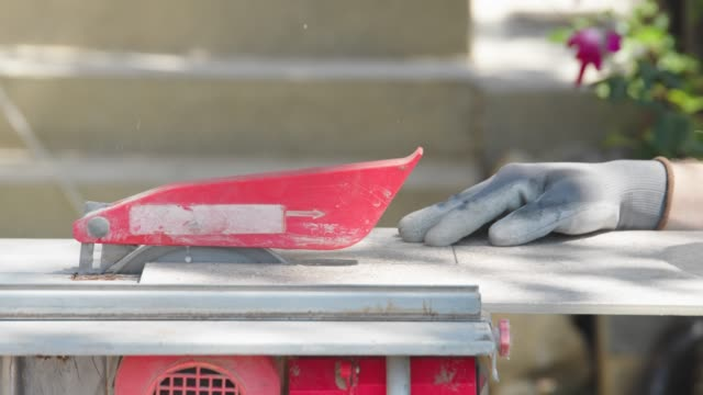 vídeos de stock e filmes b-roll de cutting a tile on circular saw - cerâmica