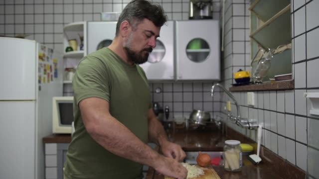 vídeos de stock, filmes e b-roll de cortar uma cebola - cebola