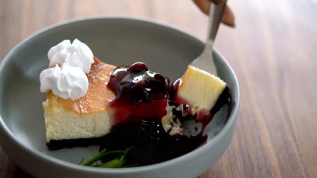 vídeos de stock, filmes e b-roll de bolo de queijo de mirtilo corte com garfo na mesa de madeira - decoração