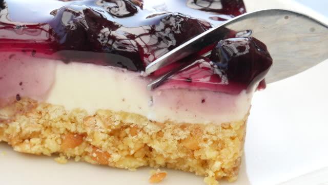 vídeos de stock, filmes e b-roll de mirtilo corte cheesecake - garfo