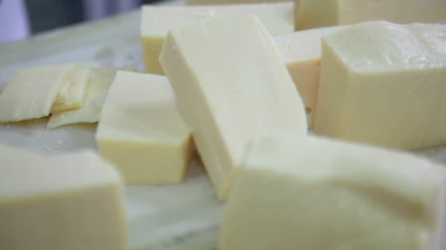 Cutting brick of cheese into slices