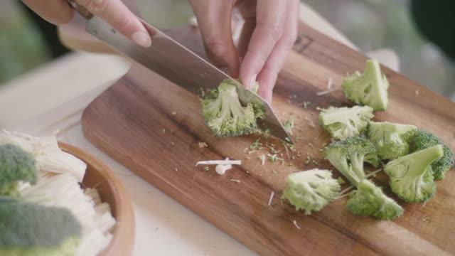 stockvideo's en b-roll-footage met het snijden van broccoli op een snijplank voor ontbijt op kampeerreis. - sperzieboon