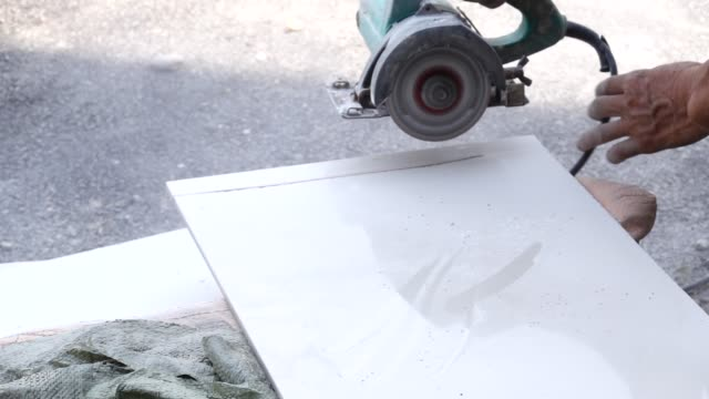 stockvideo's en b-roll-footage met het snijden van ceramische tegel met handmolen - tegel