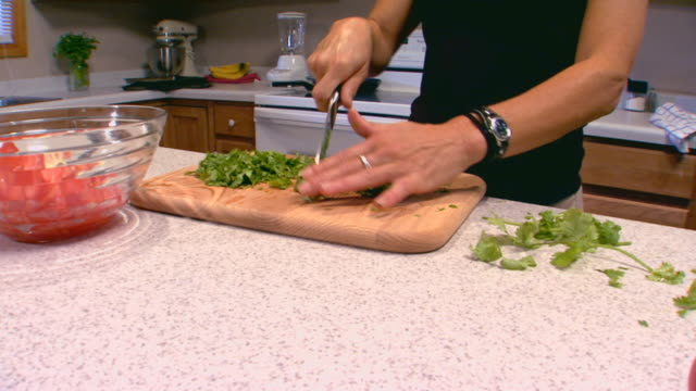 cutting cilantro and putting it into bowl - cilantro stock videos and b-roll footage