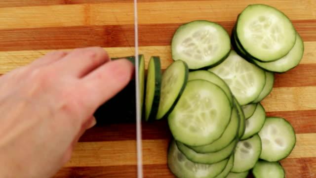 Cutting cucumber in kitchen.