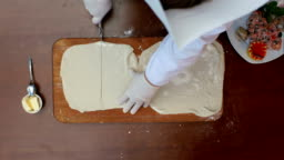Cutting dough with roller knife for ravioli on table