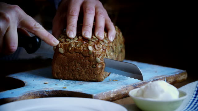 cutting fresh homemade brown bread - brown bread stock videos and b-roll footage