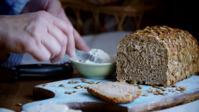 vídeos de stock e filmes b-roll de cutting fresh homemade brown bread - pão de fermento