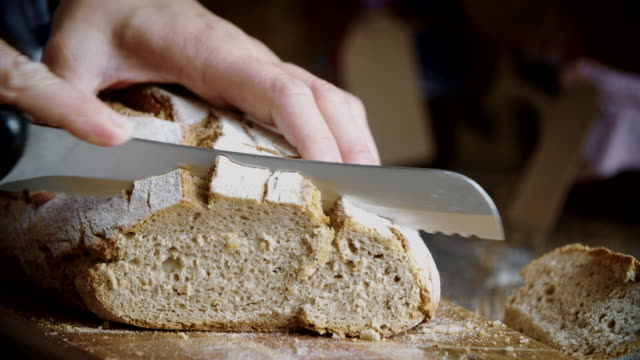 cutting fresh homemade brown bread - pane a lievito naturale video stock e b–roll