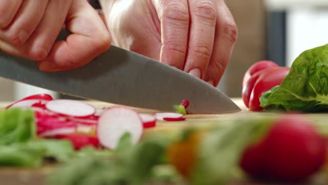 vidéos et rushes de coupes radis frais pour la préparation de salade - salade verte