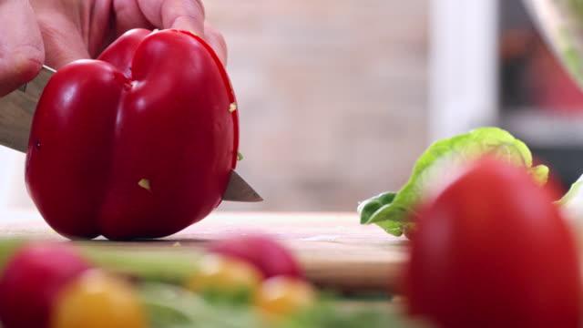 vidéos et rushes de coupe fraîche poivron rouge pour la préparation de salade - salade verte