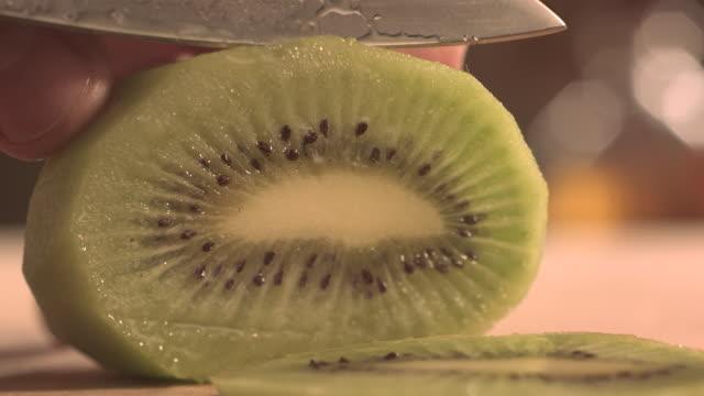 Cutting kiwi fruit with knife.