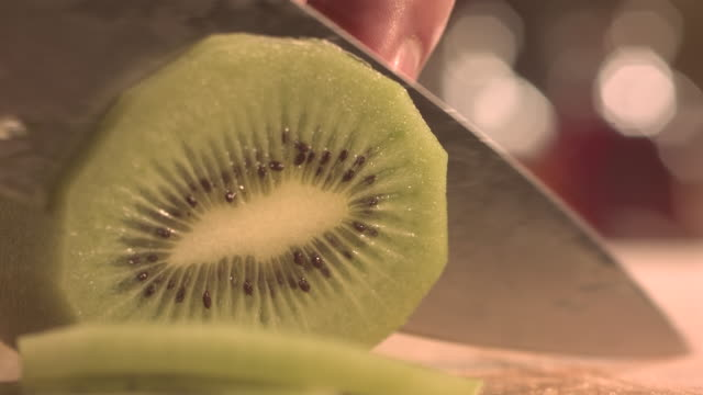 cutting kiwi fruit with knife. - kiwi fruit stock videos and b-roll footage