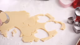 Cutting out shapes from sugar cookie dough with cookie cutters.