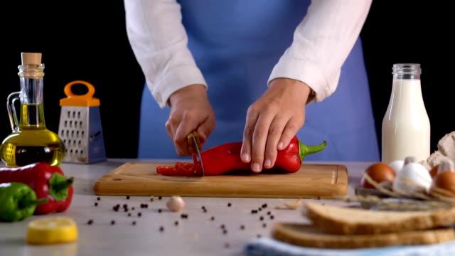vídeos de stock, filmes e b-roll de cortando a pimenta vermelha na câmara de desbastamento slow motion - corte transversal