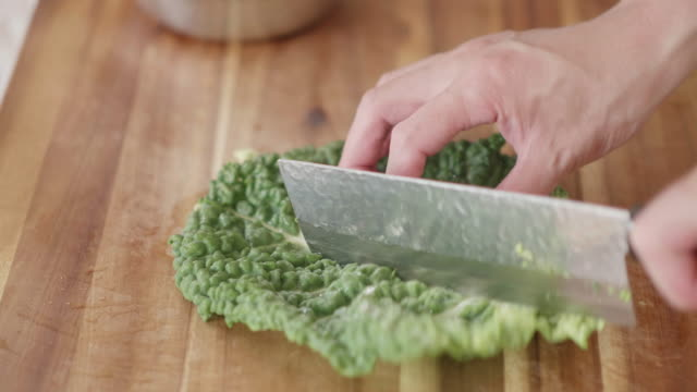 cutting savoy cabbage on wooden cutting board - savoy cabbage stock videos & royalty-free footage