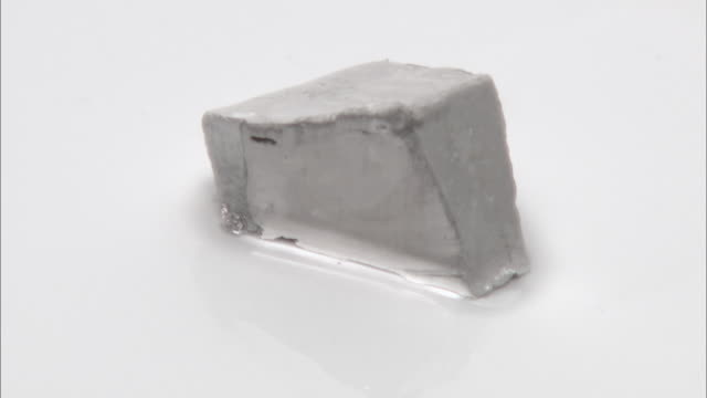 vídeos de stock e filmes b-roll de cutting sodium metal with a scalpel. the shiny exposed metal surface reacts rapidly with oxygen and water in the air, forming a duller layer of sodium oxide and hydroxide - sódio