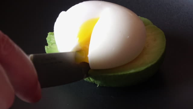 cutting soft boiled egg over avocado - egg stock videos & royalty-free footage