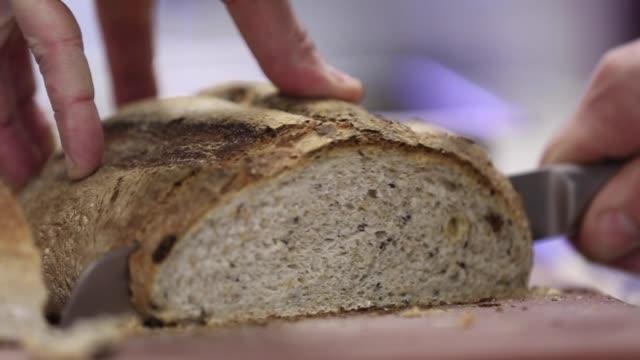 cutting sourdough bread in a cutting board - サワードウパン点の映像素材/bロール
