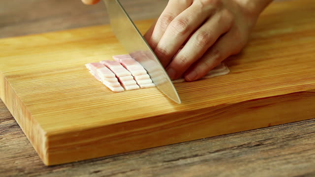 stockvideo's en b-roll-footage met cutting strips of bacon on cutting board - huishuidkunde