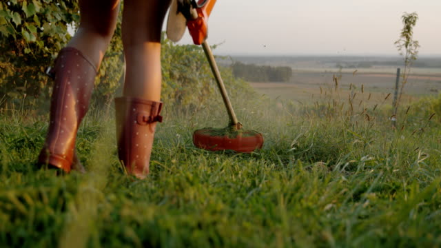 slo mo cutting the grass with a weed trimmer - mowing stock videos & royalty-free footage