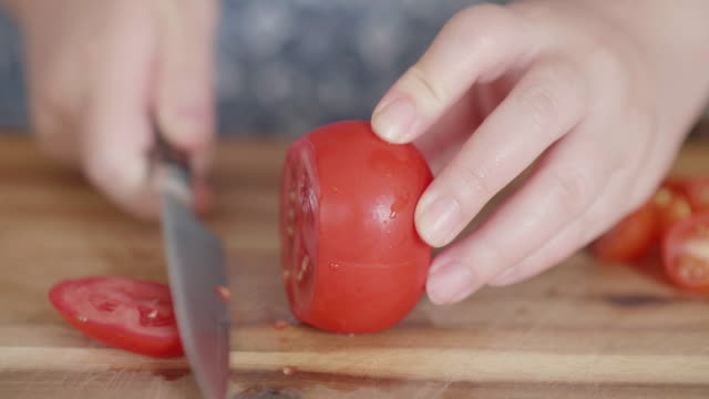 cutting tomato on wooden board - kitchen knife stock videos & royalty-free footage