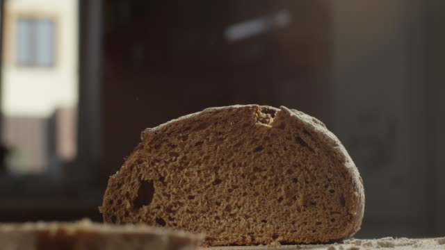 cutting with a knife crusty artisan bread in the kitchen on a sunny day shot on red camera - cutting stock videos & royalty-free footage